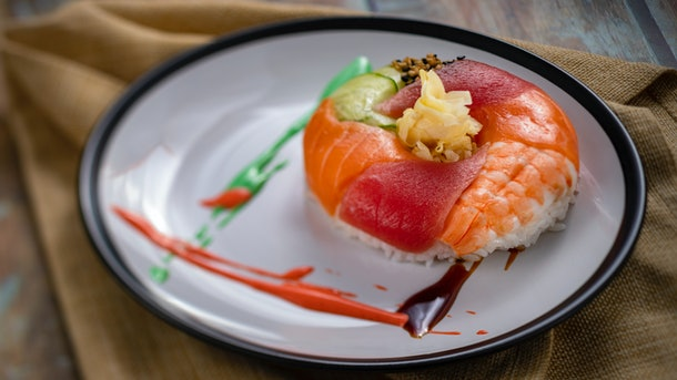 The donut-shaped sushi served at Epcot's International Festival of the Arts sits on a white plate.