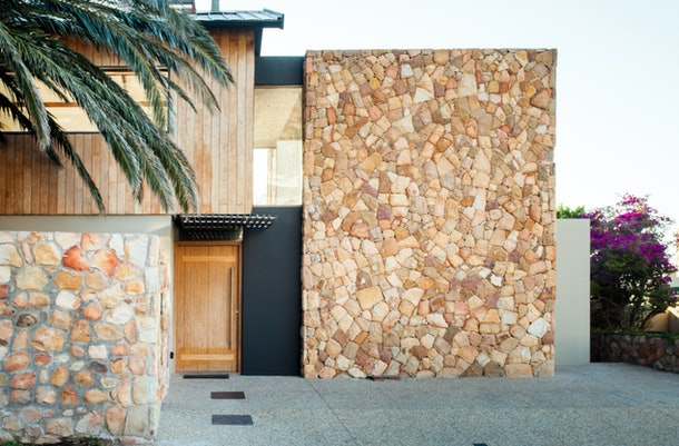 A charming studio in Cape Town, South Africa has a stone and black exterior and a giant palm tree near the front entrance.