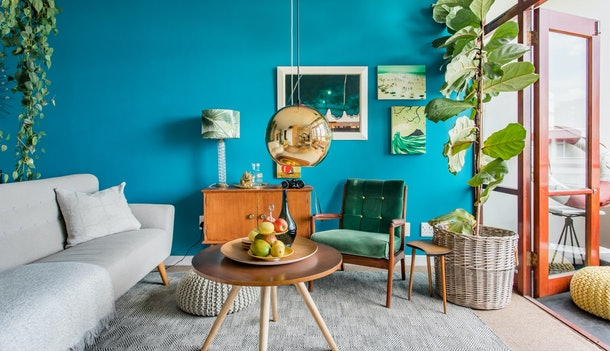 The living room of a colorful apartment in Cape Town, South Africa has a bright blue wall and mid-century modern decor.