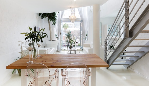 A chic loft in Cape Town, South Africa has a chandelier, hanging plants, and modern furniture.