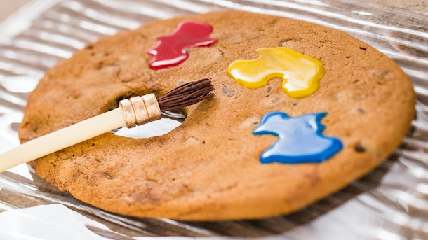 The jumbo chocolate chip cookie that looks like an artist's palette served at Epcot's International Festival of the Arts sits on a plate.