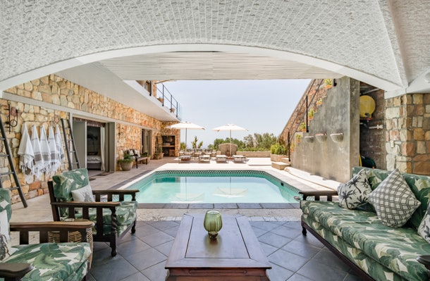 A beautiful villa in Cape Town, South Africa has a pool and palm-tree inspired furniture.
