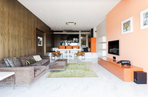 The living room of a luxe apartment in Cape Town, South Africa has a peach wall and bold style.