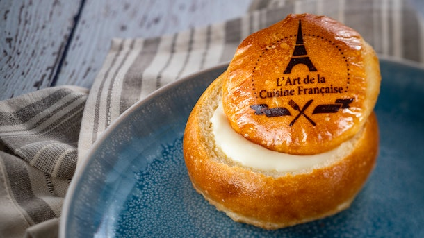 Brie in a homemade bread bowl served at Epcot's International Festival of the Arts sits on a plate.