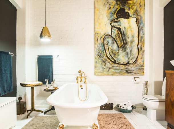 An artsy loft in Cape Town, South Africa has a luxurious bathtub and large paintings on the walls.