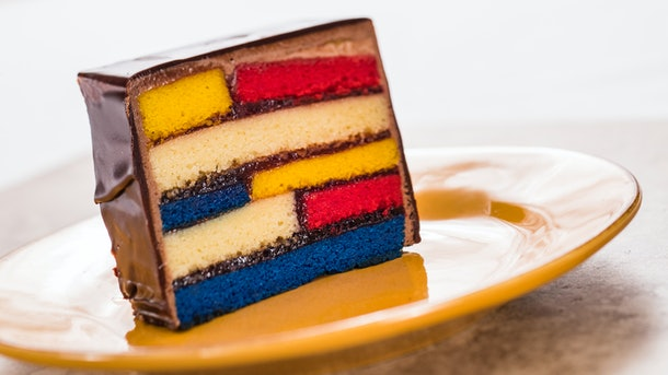 A slice of the Almond Frangipane Cake served at Epcot's International Festival of the Arts with bright colored layers sits on a plate.