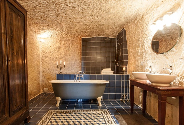 A blue bathtub sits in the center of a blue tiled bathroom in a cave home on Airbnb.