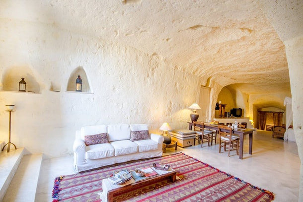 A living room in a cave home on Airbnb has a bright red and purple rug with a white couch.