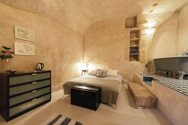 A bed and vintage bathtub are all in one cozy room in a cave home on Airbnb.