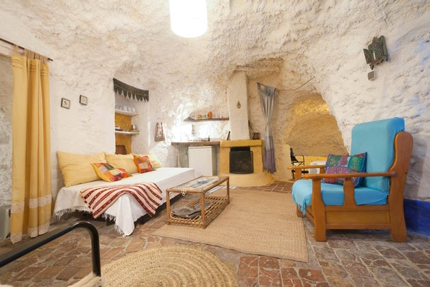 The living room in a cave home in Spain on Airbnb has a blue chair and daybed futon.