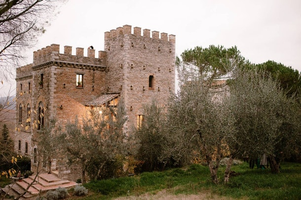 This medieval castle listed on Airbnb is surrounded by trees in the countryside of Florence.