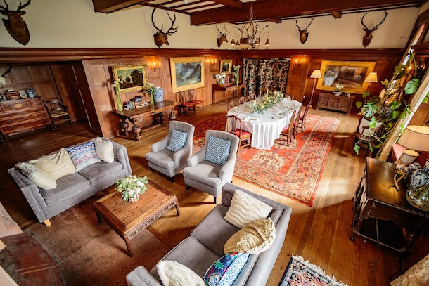 The living room in the castle listed on Airbnb has animals on the wall, a large dining table, and plush couches.