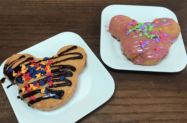 Two Mickey-shaped beignets sit on plates with strawberry and chocolate drizzle with Mickey Mouse sprinkles.