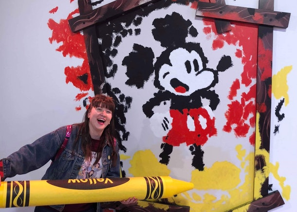 A woman holds up a yellow crayon to a wall with a Mickey Mouse portrait.