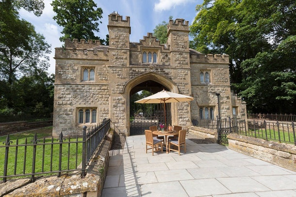 A table sits outside of the castle gatehouse listed on Airbnb with chairs and an umbrella.