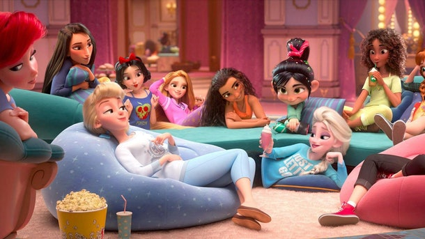A big group of Disney princesses hangs out in a living room in their PJs in a scene from 'Ralph Breaks the Internet.'