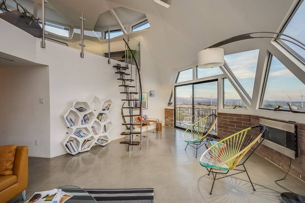 A living room has circular chairs, a small spiral staircase, and an artsy bookshelf in a dome home in Palm Springs.