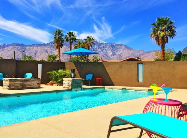 A pool with bright blue lounge chairs has mountains in the background in Palm Springs.