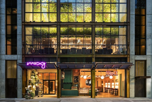 The exterior of Moxy Chelsea at night features neon lights and looks into its chic interior.