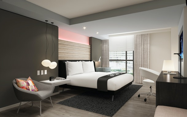 A guest room at Hotel Zena has modern decor, a view of the city, and a light pink accent wall.