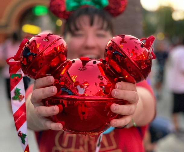 A woman holds out her shiny red Mickey-shaped popcorn bucket she bought at Disneyland.