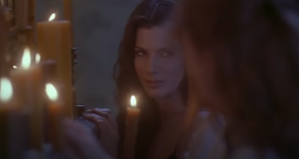 Sandra Bullock smiles next to a table of candles in the movie 'Practical Magic.'