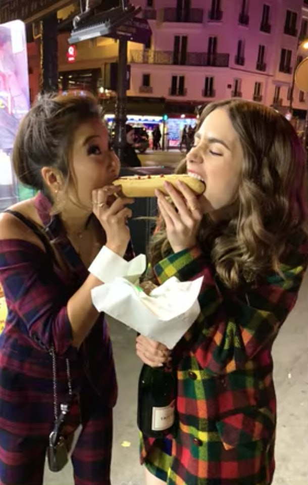 Emily (Lily Collins) and Mindy (Ashley Park) bite out of a hot dog at the same time like in 'Lady and the Tramp.'