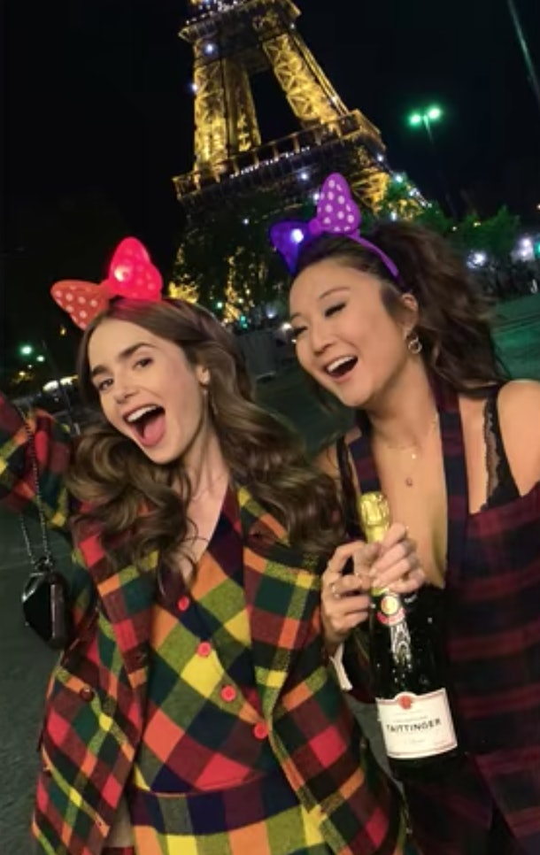 Emily (Lily Collins) and Mindy (Ashley Park) pose with a bottle of champagne in front of the Eiffel Tower in Paris.