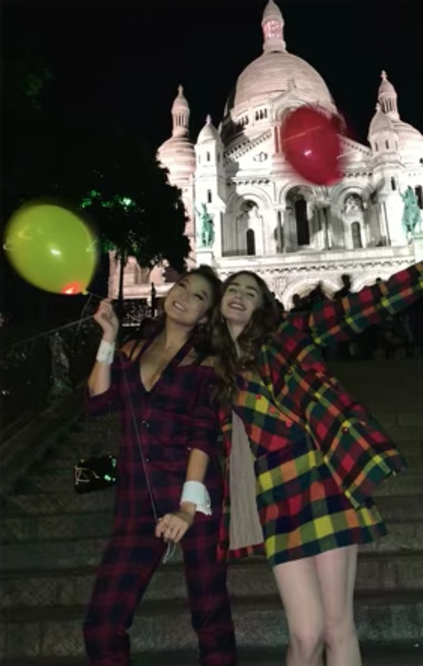 Emily (Lily Collins) and Mindy (Ashley Park) pose with balloons in their hands.