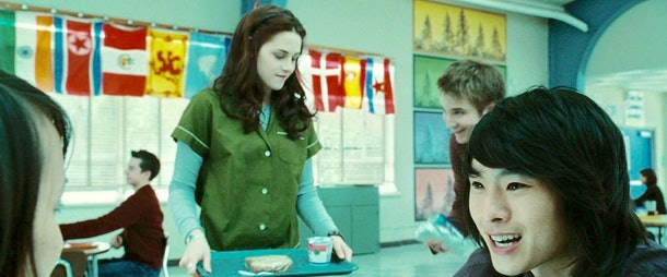 Bella walks into the cafeteria holding a tray of food to sit with Angela, Eric, and Mike.