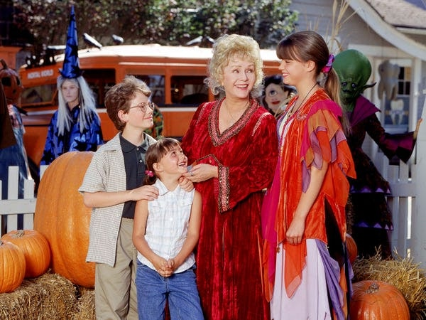 The main characters from 'Halloweentown' gather in the town square, surrounded by bales of hay and pumpkins.