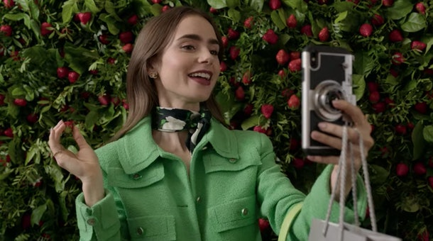 Emily (Lily Collins) takes a selfie with a berry.