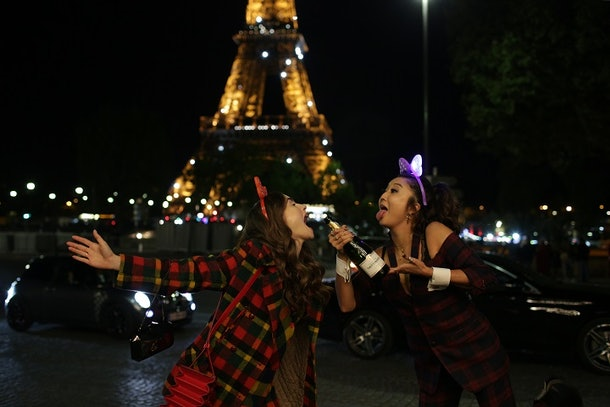 Emily and Mindy from 'Emily in Paris' wear plaid and make silly faces while holding a champagne bottle in Paris.