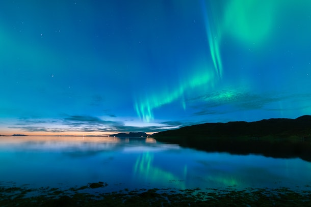 The Northern Lights light up a blue sky over a lake in Norway.