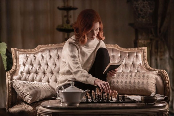 Beth Harmon (Anya Taylor-Joy) holds a chess book in her hand, while studying a game at home on her couch in 'The Queen's Gambit.'