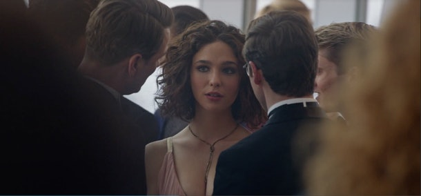 Elena from 'The Undoing' wears a light pink dress while chatting with a group of men at a fancy party.