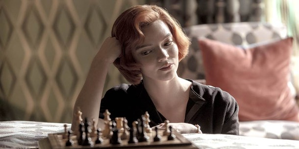 Beth Harmon (Anya Taylor-Joy) stares at a chess board, sitting on a bed, and contemplates her next move in 'The Queen's Gambit.'