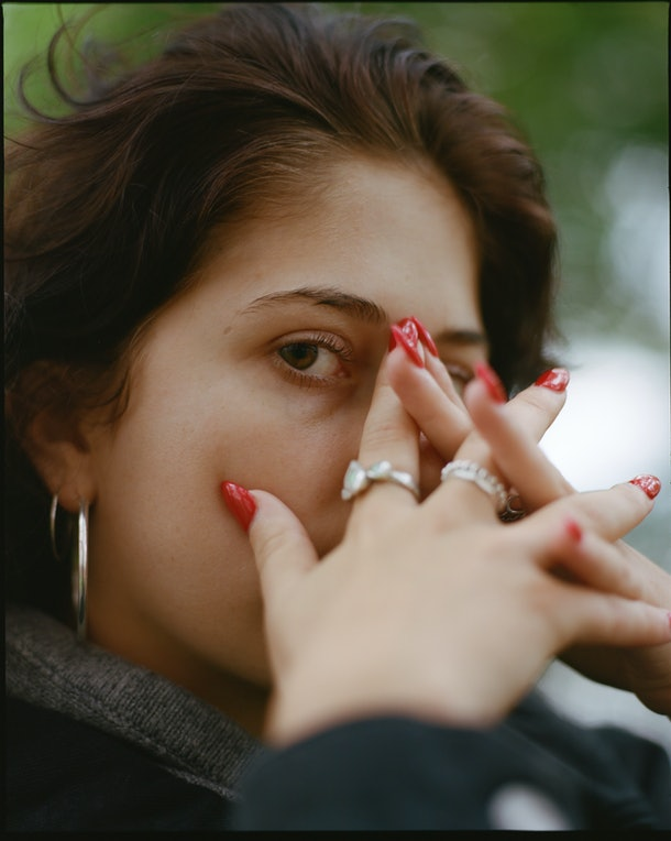 Young woman covering her face