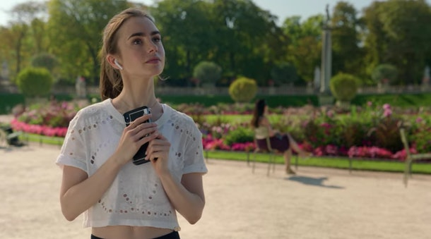 Emily (Lily Collins) stops to take a picture of a statue while going for a scenic run in Paris.