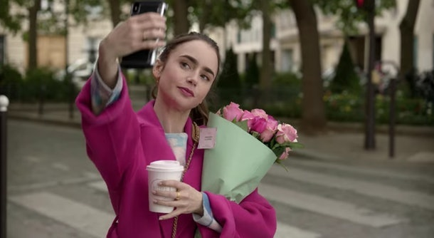 Emily (Lily Collins) snaps a selfie with a bouquet of pink roses on a Paris street.