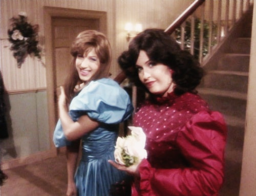 Monica (Courteney Cox) and Rachel (Jennifer Aniston) pose in front of a staircase for their prom photos in 'Friends.'