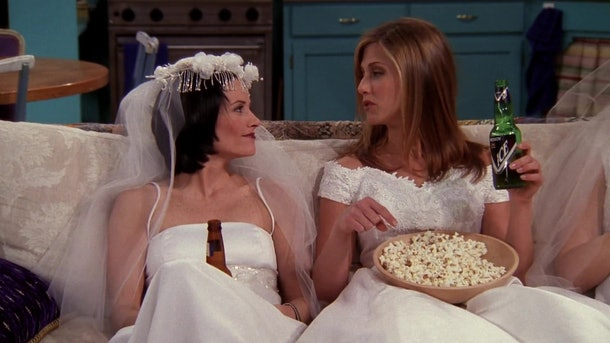 Monica (Courteney Cox) and Rachel (Jennifer Aniston) chill on the couch in wedding dresses, eating popcorn on 'Friends.'