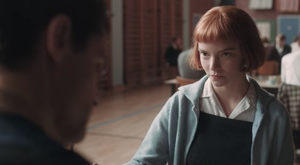 Beth Harmon (Anya Taylor-Joy) plays against D.L. Townes (Jacob Fortune-Lloyd) in a chess game tournament held in a gym in 'The Queen's Gambit.'