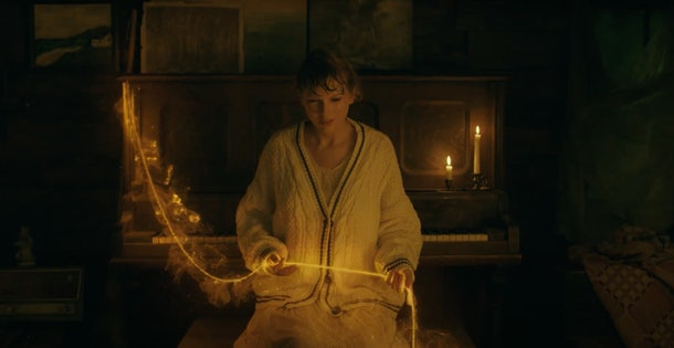 """Taylor Swift holds a gold strand in her hands while sitting at a piano bench and wearing a cardigan in the """"willow"""" music video."""
