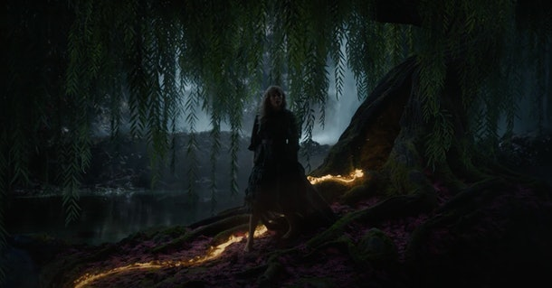 """Taylor Swift walks in the woods at night along a gold lava trail in the """"willow"""" music video."""