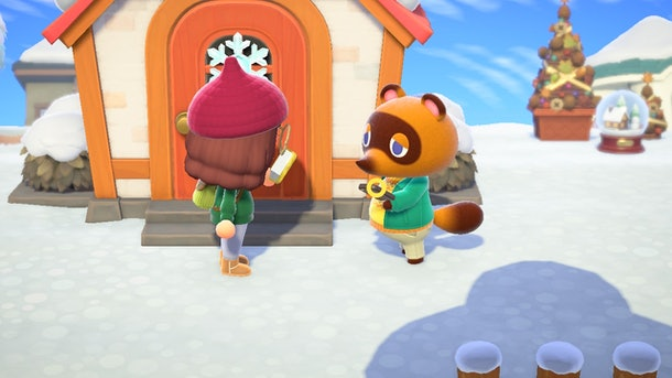 A girl character exchanges a DIY recipe with Tom Nook for a snowflake wreath in 'Animal Crossing: New Horizons'.