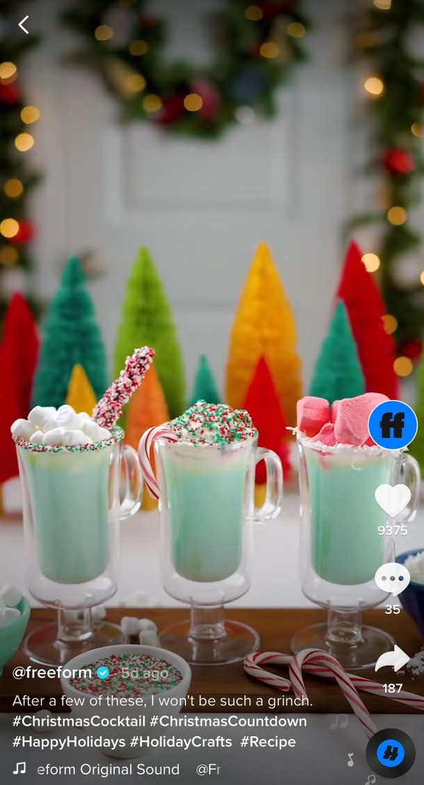 Three green hot chocolate drinks sit on a white board with festive garnishes on top.