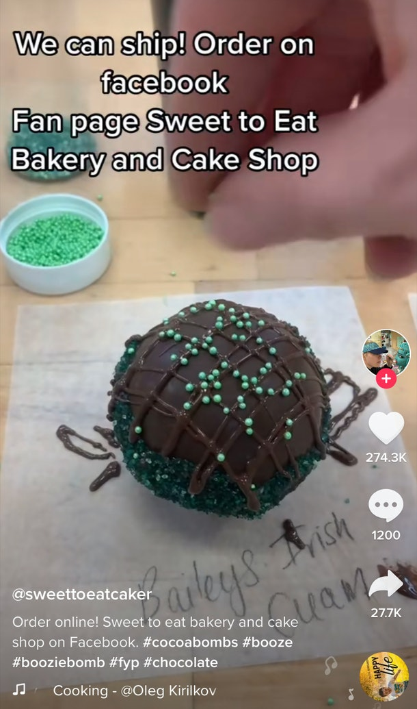 Someone sprinkles green sprinkles on top of a Baileys hot chocolate bomb.