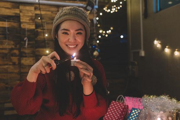 Young woman lighting Christmas candle