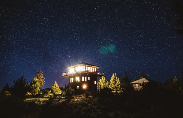 A tower listed on Airbnb sits in the woods with great views at night.
